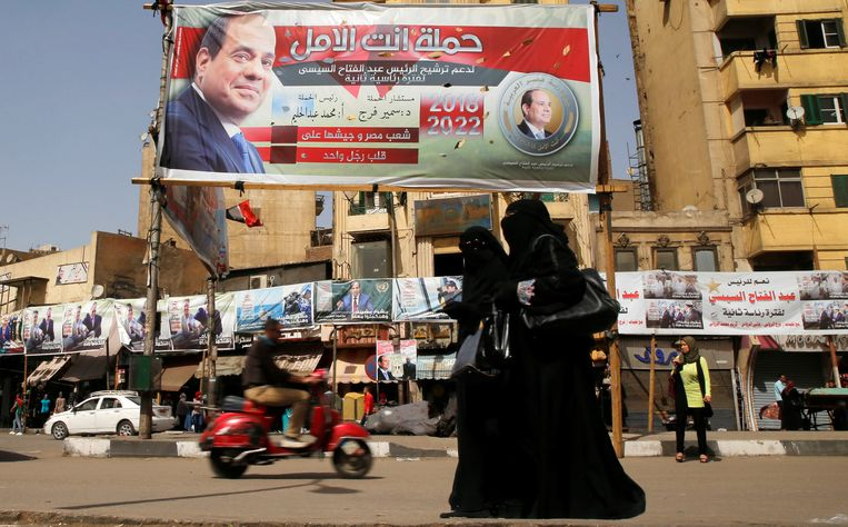 Woman wearing a full veil (niqab) walk in front of posters of Egypt's President Abdel Fattah al-Sisi during the preparations for tomorrow's presidential election in Cairo, Egypt March 25, 2018. REUTERS/Ammar Awad Beeld Reuters