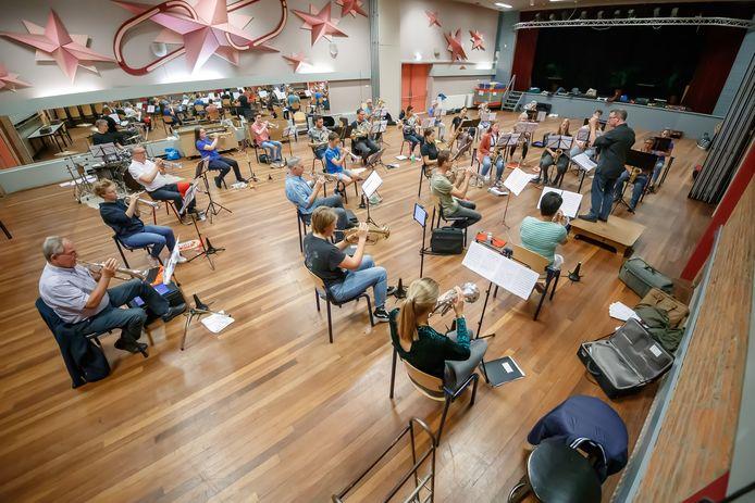 Muziekvereniging St. Caecilia in Hoeven repeteert weer ondanks corona. De orkestleden moeten wel de 1,5 meter afstand houden, dus hebben geluk dat ze in de grote zaal van het Kompas kunnen spelen.