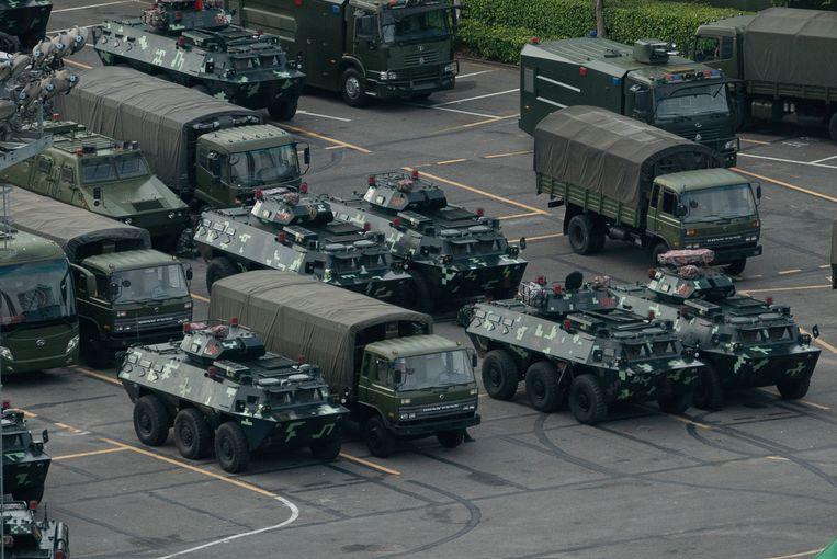 In het sportstadion van Shenzhen, een Chinese stad vlak bij Hongkong, staan de pantservoertuigen al opgesteld.
