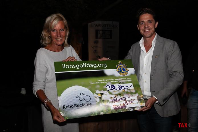 Voorzitter Jan Willem Brummelman van Lions Kwartier Arnhem overhandigt een cheque met een waarde van 33.000 euro aan voorzitter Grace Roetert van Stichting Gaandeweg. Het bedrag was de opbrengst van de jaarlijkse golfdag.