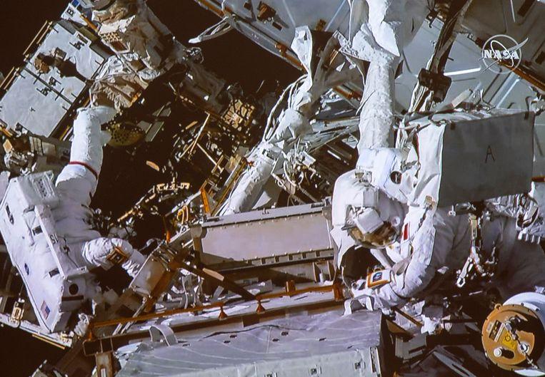 Canadese astronaut David Saint-Jacques, rechts, en NASA astronaut Anne McClain tijdens een ruimtewandeling. Beeld AP