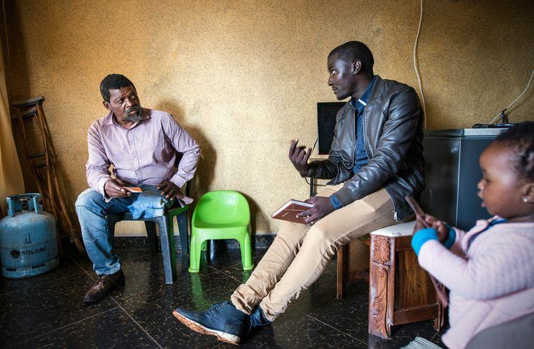 Mike Mahlangu in gesprek met Absalam Zwane wiens been in 2005 werd afgezet wegens diabetes. Mahlangu speurt townships en het platteland in Zuid-Afrika af op zoek naar geamputeerde landgenoten. Beeld Bram Lammers