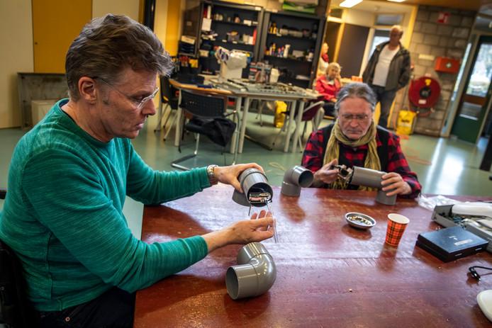 Willy van Hout (l) en Johan Megens van het Repaircafé Rijpelberg in de weer met zelfbouw-fijnstofmeters.