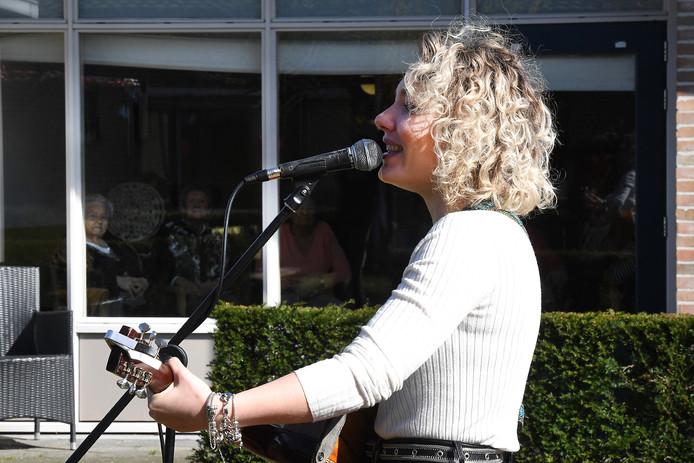 Karlijn Nijkamp zingt voor ouderen die achter de ramen zitten van zorgcentrum Pantein in Boxmeer.