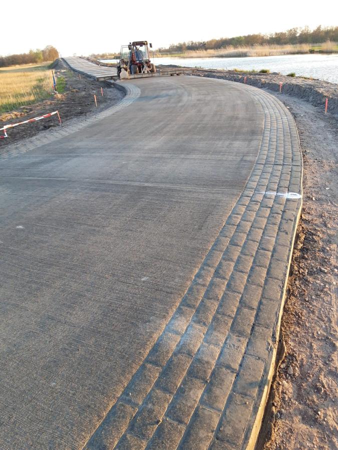 Het klinkermotief dat aan weerszijden in het beton van de Arembergerweg bij Belt-Schutsloot is 'geprint'.