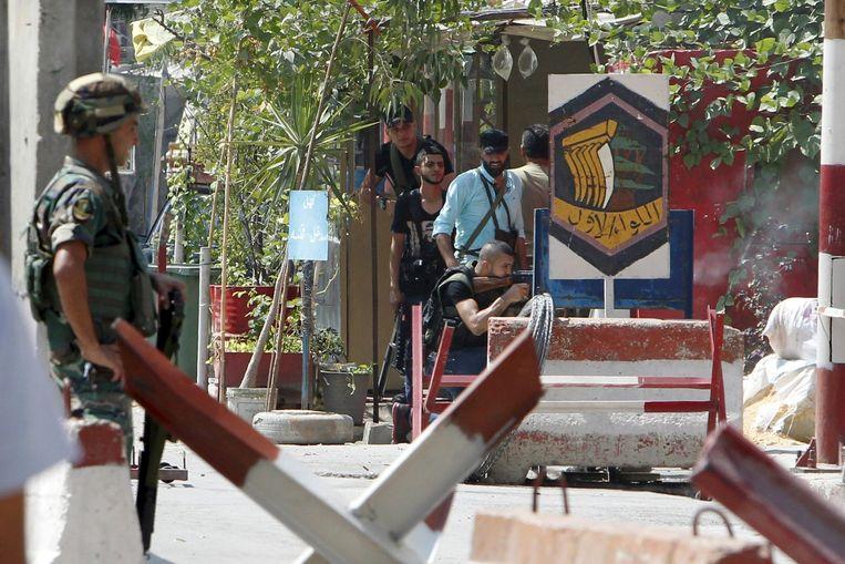 Een Libanese soldaat aan de ingang van het kamp terwijl in de achtergrond leden van de Palestijnse Fatah-beweging schieten op leden van de soennitische extremistische groep Jund al-Sham.