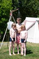 Louis, Nathan en Morris (vlnr) onder de buitendouche naast de tent, op camping Bij Ons in Groesbeek.