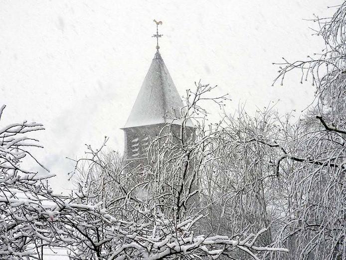 Vanuit de woonkamer van Margriet Hazendonk een mooi winters gezicht op de kerktoren van Middelbeers.