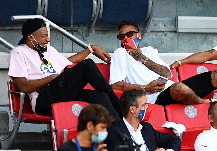 Mbappé vermaakt zich met Neymar in de tribunes tijdens de oefenmatch van PSG tegen Sochaux.