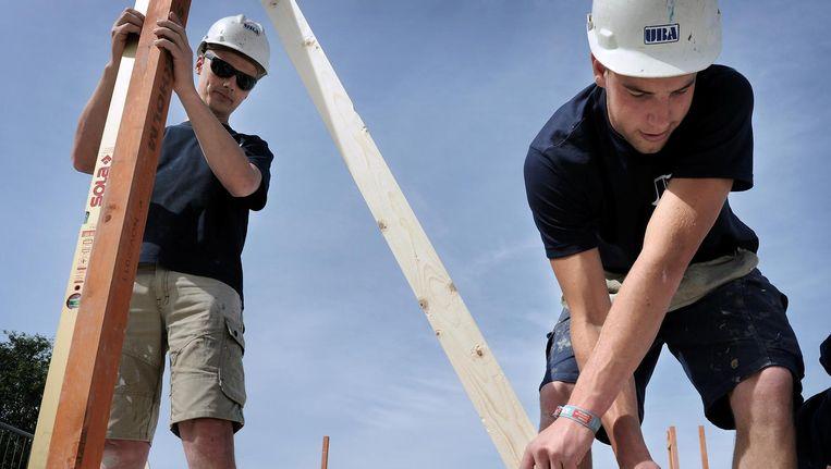 Twee bouwvakkers bij de bouw van nieuwe woningen Beeld Marcel van den Bergh/de Volkskrant
