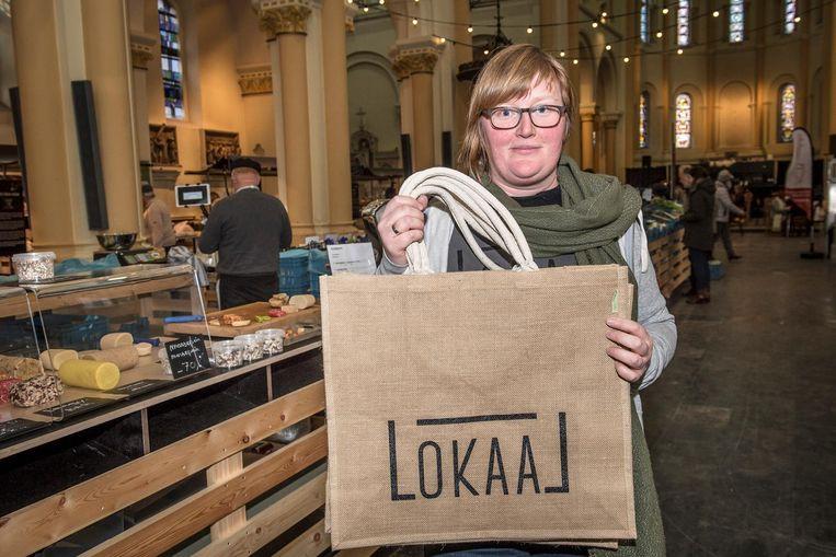 Melanie Vanstaen van de Lokaalmarkt met de winkeltassen waar klanten voor kunnen sparen.