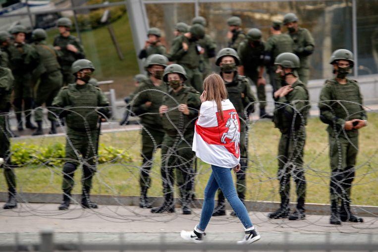 Een vrouw omwikkeld in een Wit-Russische vlag loopt langs soldaten tijdens een protest in Minsk. Beeld AP