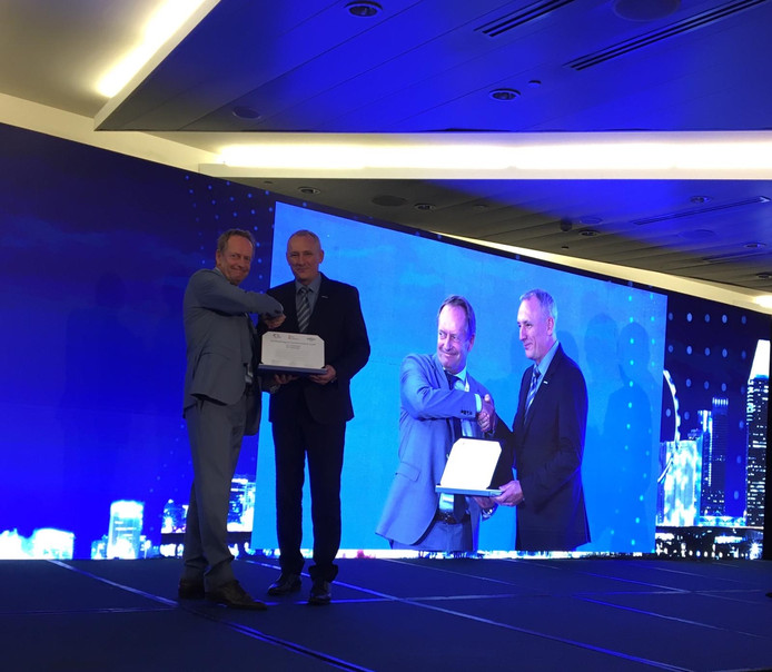 Gert Blom (links) van de gemeente Helmond krijgt in Singapore de ITS Local Government Award overhandigd.