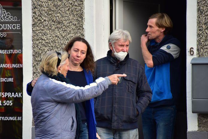Sybil Duprez (tweede van links) en haar man Denis Demets (uiterst rechts), samen met enkele familieleden op de plaats van de brand, in de Helkijnstraat in Sint-Denijs.