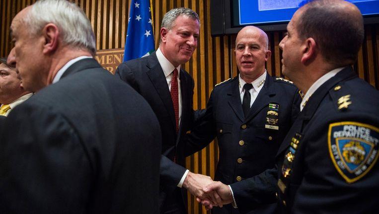 De New Yorkse burgemeester Bill de Blasio (midden) schudt politieagenten de hand bij een persconferentie na de dood van de twee agenten vorige week.