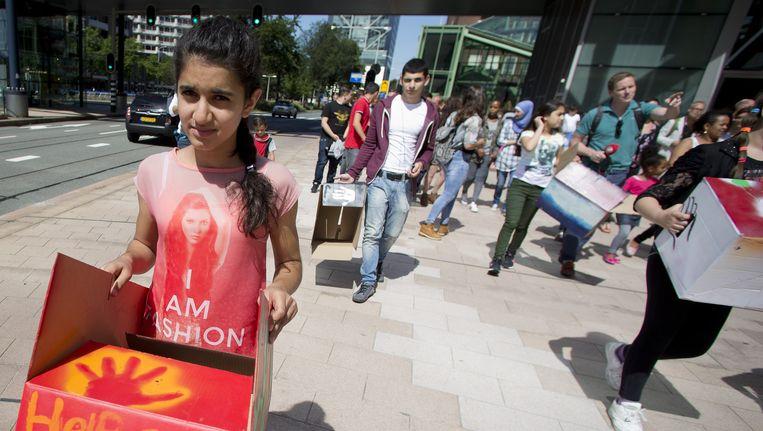 Asielzoekers en hun kinderen lopen in een protestmars vanaf Den Haag Centraal. Archiefbeeld. Beeld ANP
