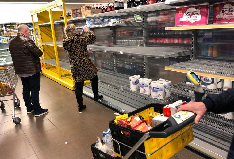 Lege schappen in de Jumbo in Tiel omdat mensen bij het begin van de lockdown gingen hamsteren. Uiteindelijk hadden de supermarkten 40 procent meer pinomzet in april.  Beeld Marcel van den Bergh / de Volkskrant