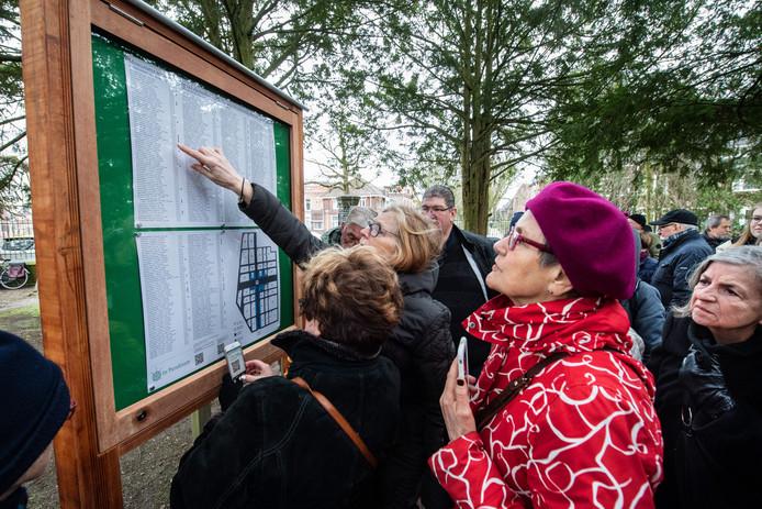 Bezoekers bestuderen het nieuwe oorlogsmonument in Nijmegen.