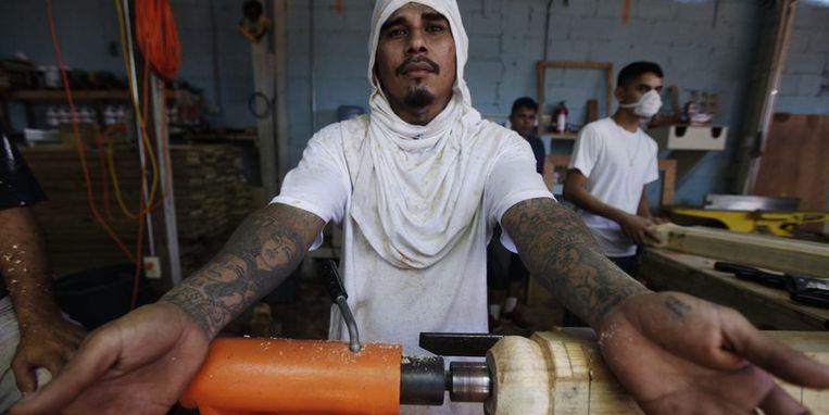 Een man op de timmerwerkplaats van de gevangenis laat zijn tatoeages zien. Beeld reuters