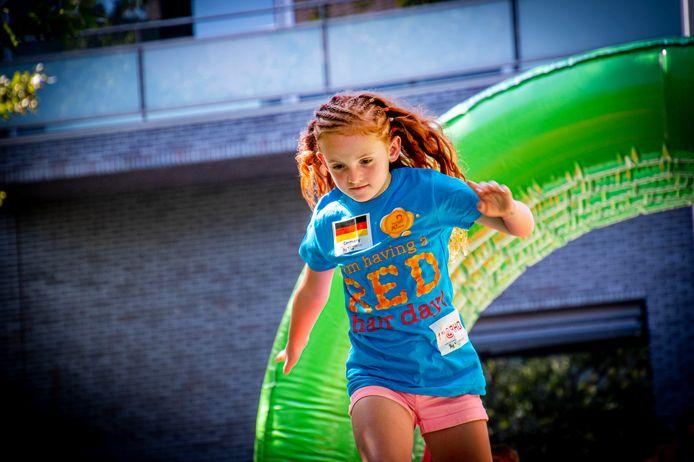 Een meisje, dat zojuist haar roodharige haarbos heeft laten vlechten, rent over de stormbaan op het Pieter Vreedeplein.