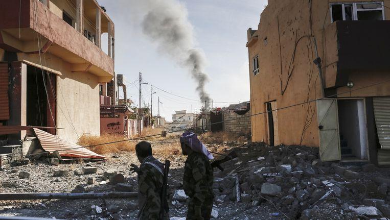 Rook boven de stad Sinjar in Irak. Koerdische- en yezidistrijders heroverden de stad afgelopen vrijdag op IS. Dat had Sinjar sinds zomer vorig jaar in handen. Beeld Sam Tarling