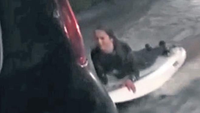 Kristie Swinkels surft achter de auto van haar vader.