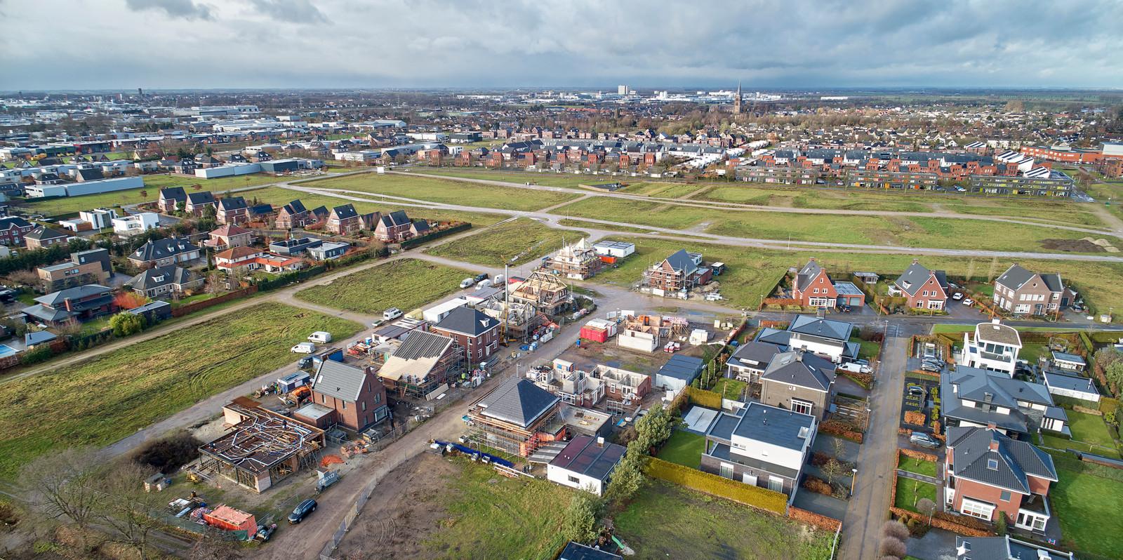 Vanuit de lucht is goed te zien waar fase vier van de nieuwbouwwijk moet verrijzen. Op de achtergrond de dorpskern van Berghem.