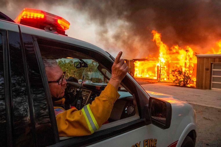 Brandweermannen arriveren bij een brandend gebouw.