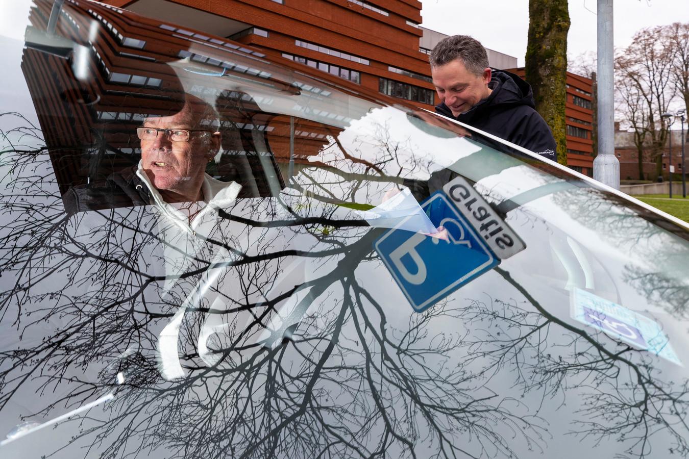 Ton Straver (links) in discussie met John Swaans, verkeersdeskundige van de gemeente Waalwijk. Ton heeft COPD. In Waalwijk Centrum grijpt hij vaak mis op een invalidenparkeerplaats.