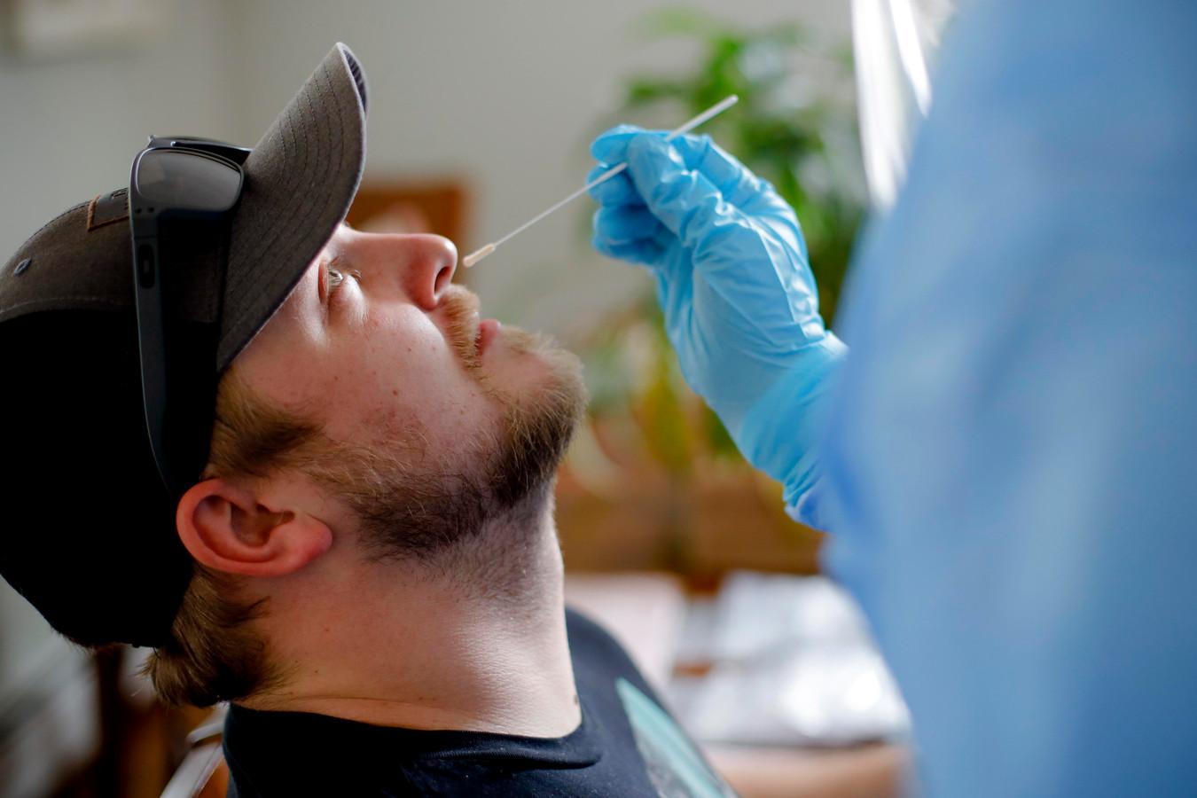 Een man wordt getest op corona door wat neusslijm af te nemen.