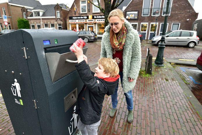 Marjolein Kostwinder met zoontje Minck (4) vullen de pratende prullenbak aan de Grote Haven in Haastrecht.