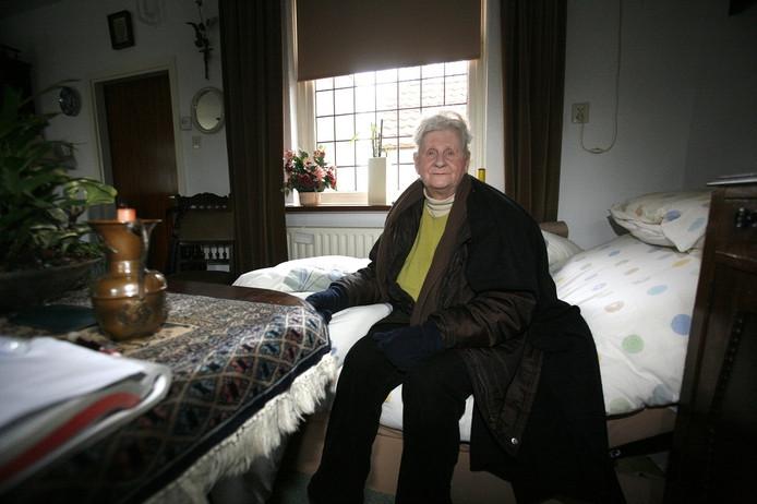 Een oudere dame in Kerkdriel heeft het koud in huis door de stroomstoring, en dus zit ze met haar jas aan de rand van het bed.