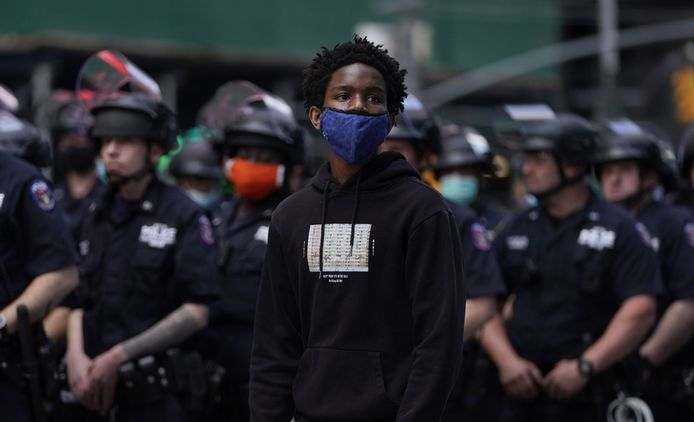 """A protestor stands in front of a police line in Times Square on June 1, 2020, during a """"Black Lives Matter"""" protest. - New York's mayor Bill de Blasio today declared a city curfew from 11:00 pm to 5:00 am, as sometimes violent anti-racism protests roil communities nationwide. Saying that """"we support peaceful protest,"""" De Blasio tweeted he had made the decision in consultation with the state's governor Andrew Cuomo, following the lead of many large US cities that instituted curfews in a bid to clamp down on violence and looting. (Photo by TIMOTHY A. CLARY / AFP)"""