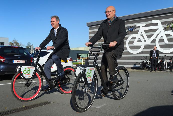 Gedeputeerde Harry van der Maas (l) en wethouder Chris Simons op deelfietsen.