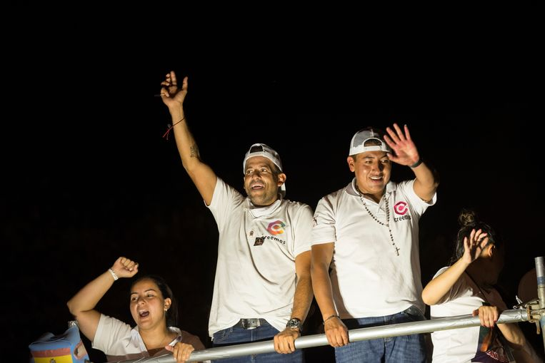 Presidentskandidaat Luis Fernando Camacho (links) en zijn partijgenoot Marco Pumari van de rechtse partij Creemos zwaaien naar hun aanhangers bij hun campagne woensdag in Santa Cruz. Beeld Marcelo Perez del Carpio