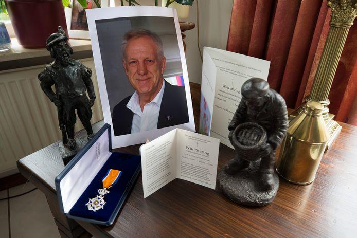 Een foto van Wim Staring, zijn lintje en twee bronzen beeldjes.