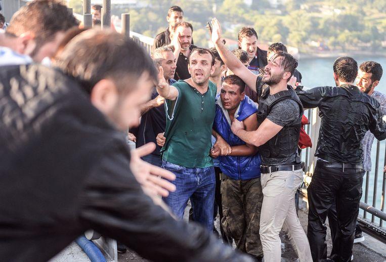 Juli 2016: een soldaat (in blauw shirt) die meedeed aan de couppoging in Turkije wordt in Istanbul door omstanders in de kraag gevat. Beeld AP