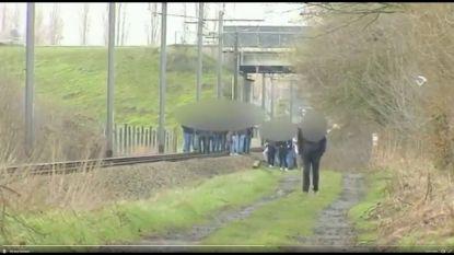 Klas en begeleider lopen over treinsporen