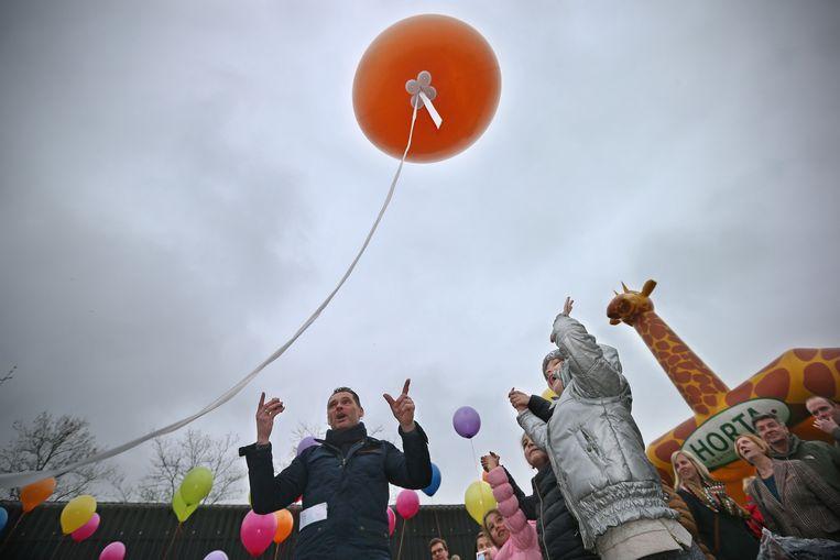 Kinderen zetten hun duimafdruk op de oranje ballon.