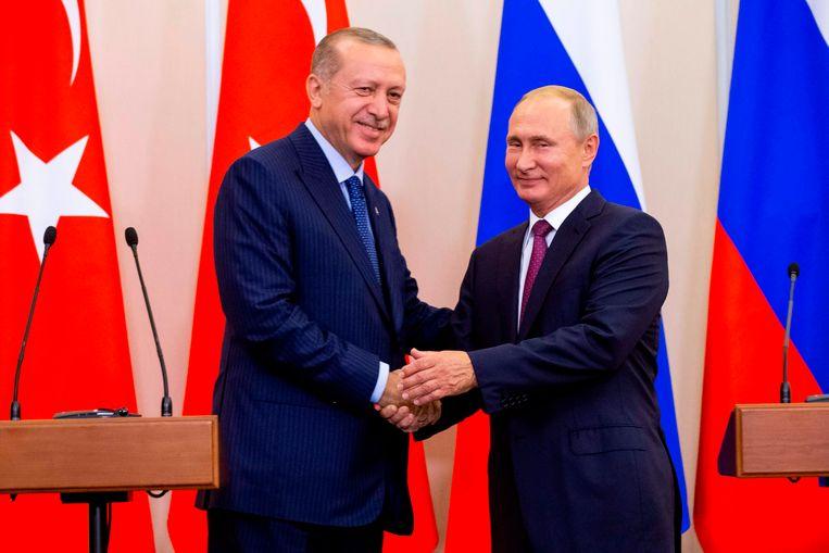 De Russische president Vladimir Poetin en zijn Turkse collega Recep Tayyip Erdogan geven elkaar de hand. Beeld AFP