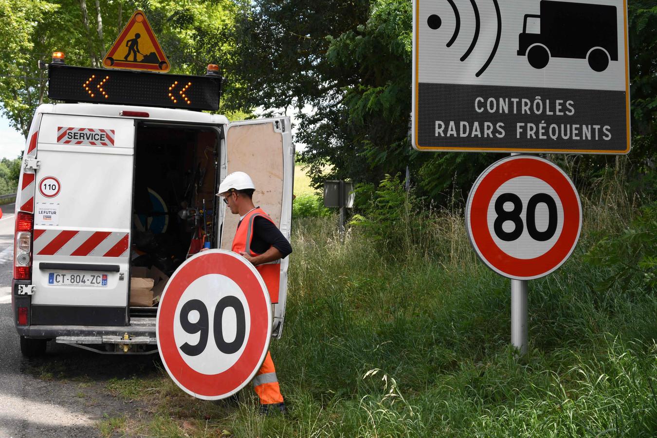28 juni 2018: een wegwerker vervangt langs een Franse departementale weg  het 90 km/u-bord door een 80 km/u-bord.