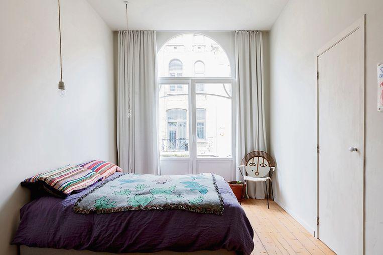 Op het bed liggen handgemaakte kussens en een plaid van BFGF. De spiegel komt van de beurs Maison et Objet.