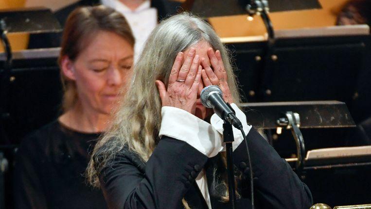 Patti Smith verbergt haar gezicht tijdens de uitreiking van de Nobelprijs voor de literatuur aan Bob Dylan. Beeld ap
