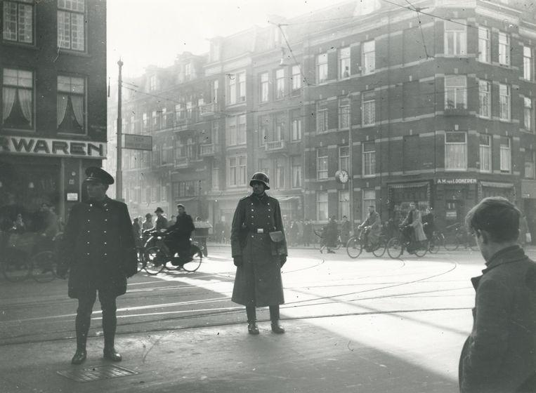 Nederlandse politieagent en Duitse soldaat in Amsterdam, 1941.   Beeld Fotograaf onbekend / NIOD, Beeldbank WO2