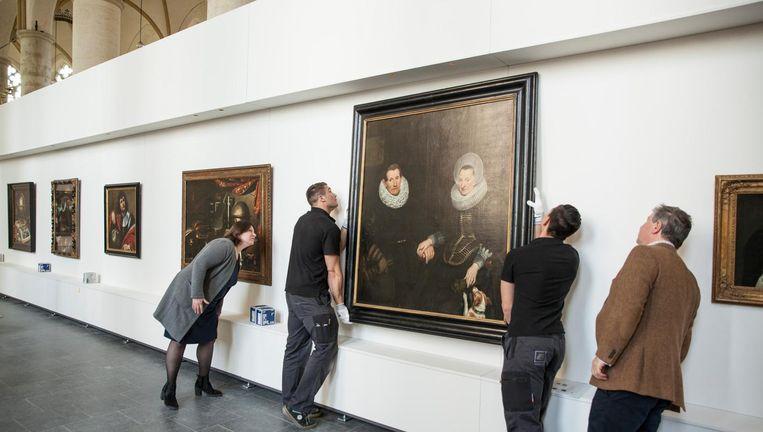 Eva Kleeman en Daaf Ledeboer controleren het ophangen van een schilderij in de Deventer Bergkerk. Beeld Harry Cock