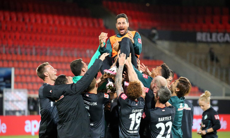 Claudio Pizarro wordt door de spelers van Werder Bremen gejonast.