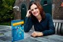 Annette van der Plas met haar boek op het terras bij Fort Vuren. Dat terras komt trouwens ook voor in het boek.