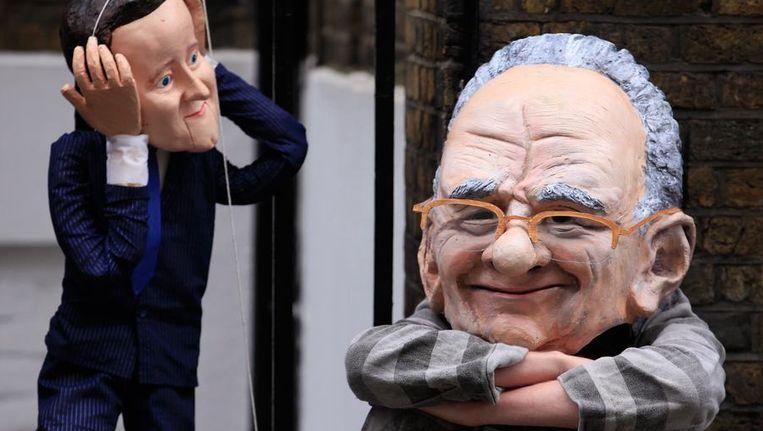 Protest met karikaturale poppen van de Britse premier Cameron (links) en Rupert Murdoch voor het appartement van Cameron, vandaag. Beeld reuters