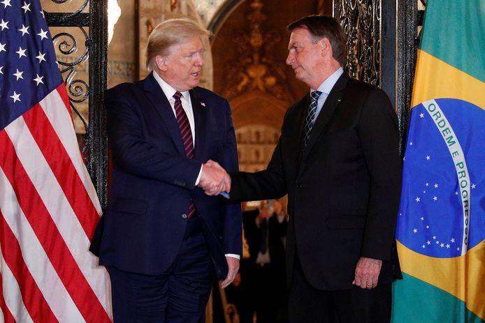 De Amerikaanse president Donald Trump schudt zijn Braziliaanse collega Jair Bolsonaro de hand, vorige week zaterdag in Florida.