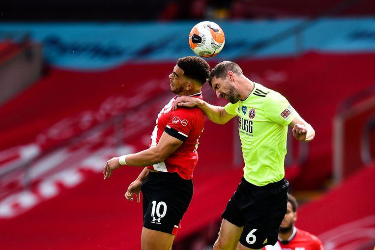 Southamptons Che Adams en Sheffield Uniteds Chris Basham botsen tijdens een kopduel.  Beeld AP